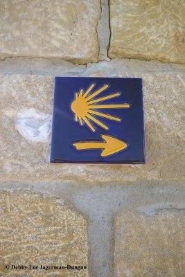 Scallop Shells And Yellow Arrows Of The Camino De Santiago