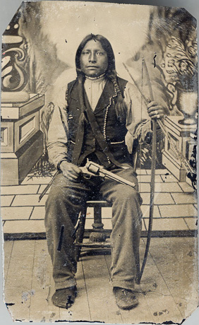 Indian seated with revolver and bow