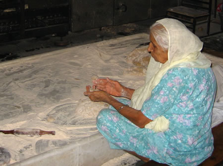 Woman making roti in Sikh temple, India