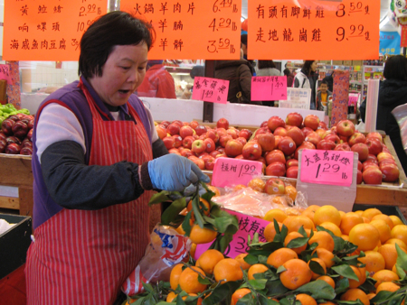 Shopkeeper with oranges, Chinatown Supermarket, Vancouver