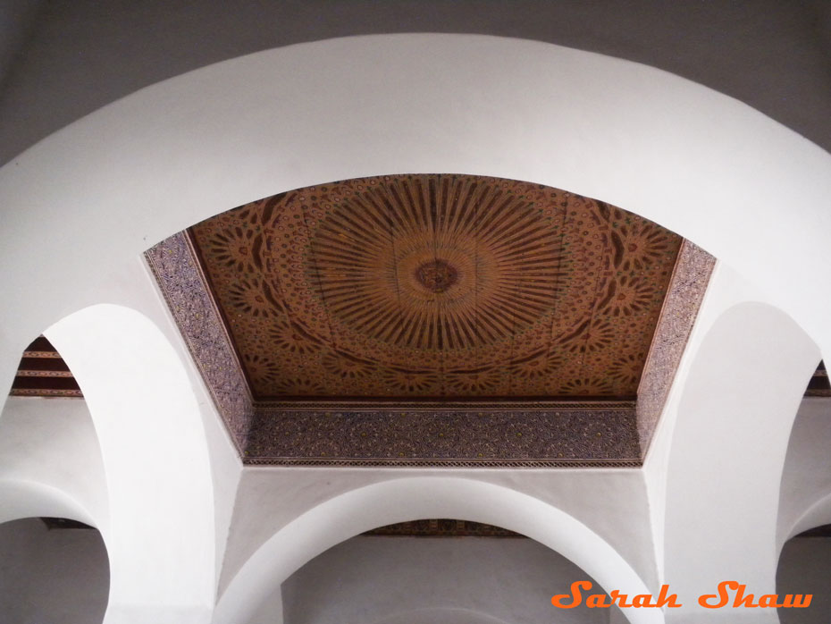 Arches surround a painted ceiling panel in Marrakesh