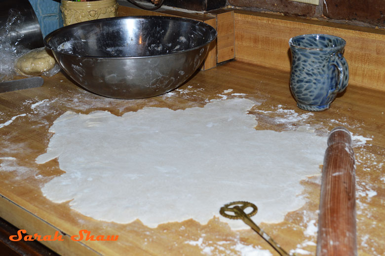 Pastry dough rolled out on a floured surface