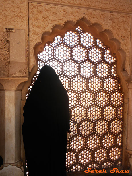 A woman gazes through a screen window at the Amber Fort in Jaipur, India