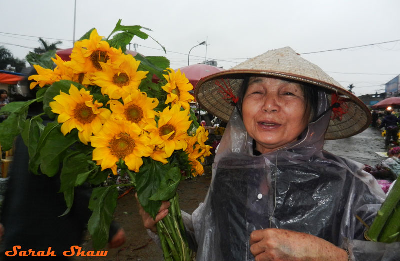 A woman buys sunflowers at Hanoi's flower market