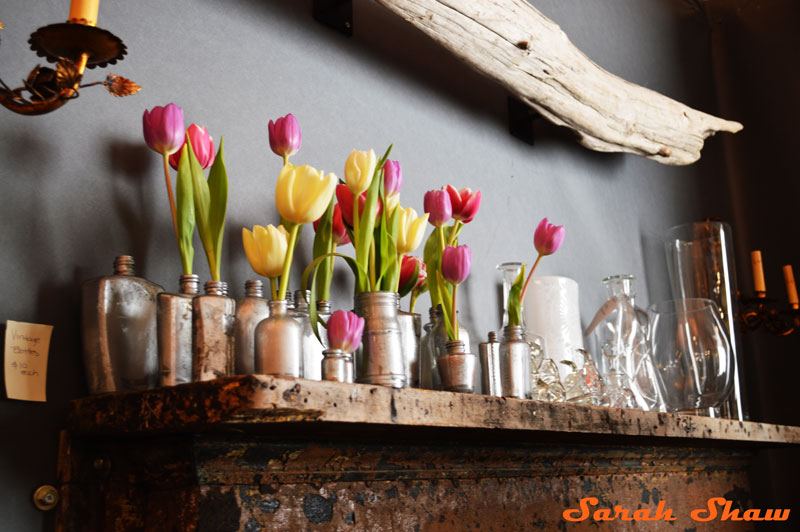 Silvered bottles and tulips create a beautiful mantle at the Antique and Garden Fair in Chicago