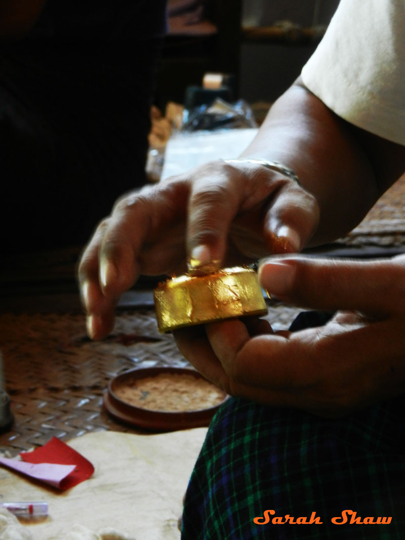 Adding gold leaf to a lacquer dish in Bagan, Myanmar