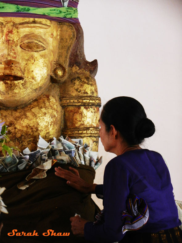 Offering money and gold leaf to a Nat in Bagan, Myanmar
