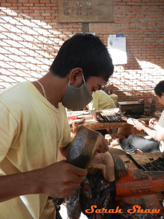 An apprentice carves at Artisans Angkor in Siem Reap