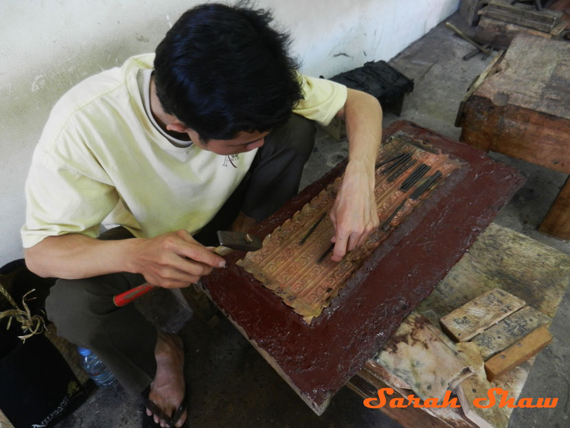 An apprentice molds silver to a form to create an embossed item at Artisans Angkor