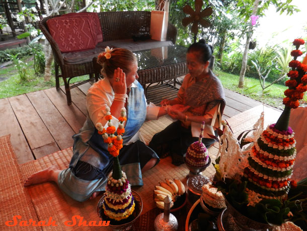 My cultural guide ties my strings on during my baci ceremony in Laos