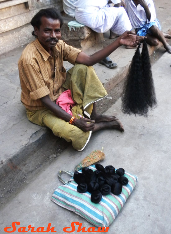 A man sells hair to be used as an offering outside a temple in Tamil Nadu, India