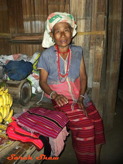 White Karen woman offers her weavings to me near Chiang Rai, Thailand