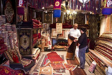 Turkish Man Selling Carpet to Female Tourist